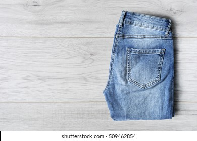 Blue jeans folded on white wooden background
