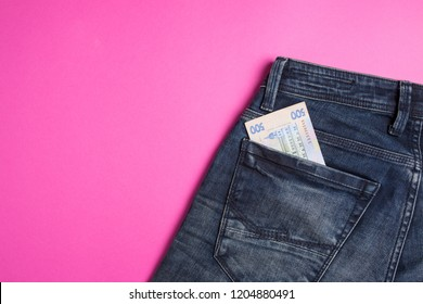 Blue jeans with hryvna banknotes on a pink background close-up
