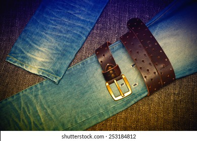 Blue jeans and a leather belt with a gold buckle. Youth trend. Photo toned in yellow and purple.