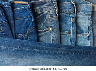 Blue jeans pants clothes pile background. Stack of blue jeans on shop desk