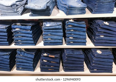 Blue Jeans pants on the store shelf. Blue jeans denim Collection jeans stacked. Jeans Showcase, sale, shopping