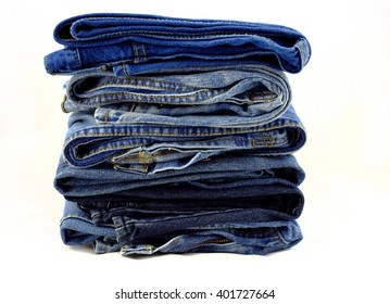 Blue jeans pants pile on a white background.