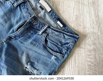 Blue jeans rested on a white wood grain background.