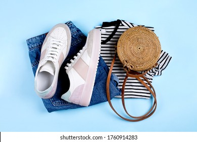 Blue jeans shorts, sneakers, striped shirt and rattan bag on blue background. Overhead view of summer woman's casual outfit. Flat lay, top view.