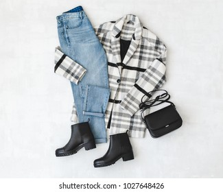 Blue jeans, striped coat, small black cross body bag and leather ankle boots on grey background. Overhead view of woman's casual day outfits. Trendy hipster look. Flat lay.
