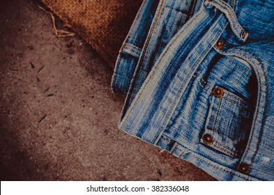 Blue jeans texture background  design On brown hemp sack,Ripped jeans of a stack Hipster fashion copy space for text commentary .