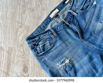 Blue jeans There is a slight tear, not zipped, placed on a white wood grain floor, view from above.