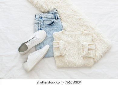 Blue jeans, white knitte sweater, sneakers and fur scarf  lying on the bed on white sheet. Overhead view of woman's casual day outfits. Trendy hipster look. Top view of women's winter clothes.