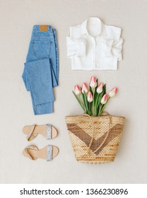 Blue jeans, white shirt, flat sandals, straw woven basket bag, bouquet of pink tulips flowers on beige background. Woman's casual spring summer outfit. Trendy women's clothes. Flat lay, top view.