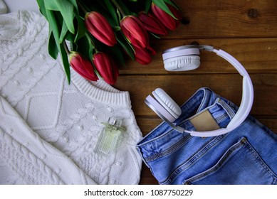 Blue jeans, women sweater, earphones? a perfume bottle and a bouquet of red tulips on a wooden background