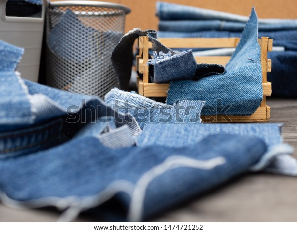 Blue jeans in a wooden crate and in bins. Recycling old denim for the circular economy.  Miniature.