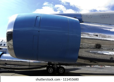 Blue jet engine with blue sky and white clouds