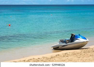Blue jetski on sand at beach in Barbados