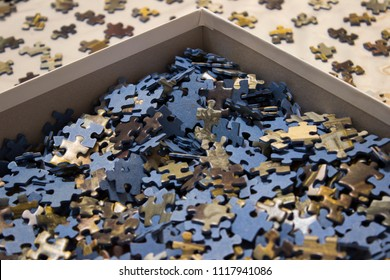 Blue jigsaw puzzle in a box, with pieces ordered face-up around it.