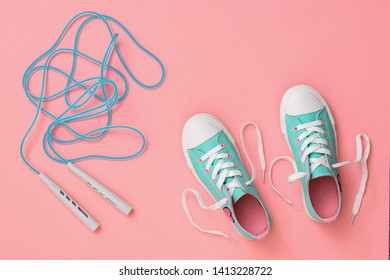Blue jump rope and sneakers on the wooden floor. Sports style. Flat lay. The view from the top.