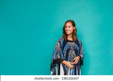 Blue kaftan girl smiling in studio, looking away