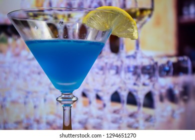Blue Kamikaze cocktail in martini glass decoreted slice of lemon