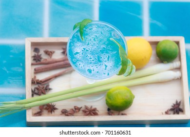 Blue kamikaze cocktail on pool background with fruits and herbs garnish