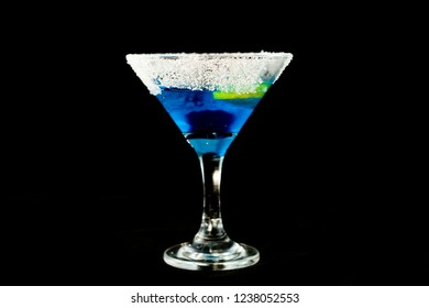 Blue kamikaze cocktail with vodka, lime juice, blue curacao, sugar and lime wedge