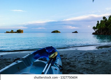 Blue kayak with yellow paddles on a deserted white sand beach at sunrise.