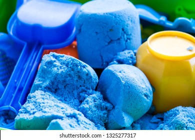 Blue kinetic sand with a small plastic shovel and toys lies in the container. Concept of development in children of fine motor skills and creative imagination. Close-up.