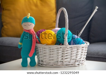 blue knitted amigurumi crochet standing near a basket of wool balls, in front of a sofa