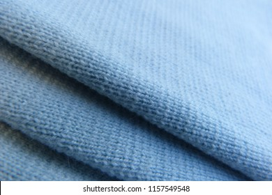 blue knitted fabric close-up soft fabric folds roll natural material background for decor blue color