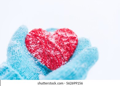 Blue knitted gloves with woolen heart. St. Valentine's Day greeting card