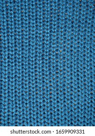 Blue knitted textured background, knit with facial loops. Hand knitting.