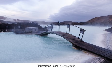 Blue Laggon in Iceland wrapped in rocks with a small bridge over the water. Blue clear water, very hot with cold air so we see a lot of steam being released. Geothermal bath resort. Natural water