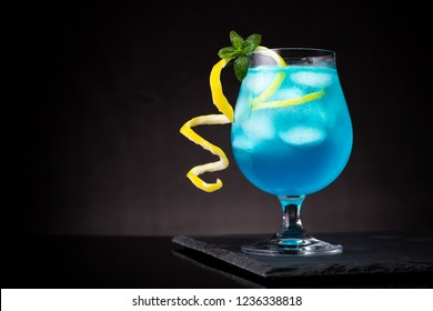 Blue lagoon cocktail with blue curacao liqueur, vodka, lemon juice and soda, decorated with lemon slice and mint leaves. Selective focus on the mint leaves
