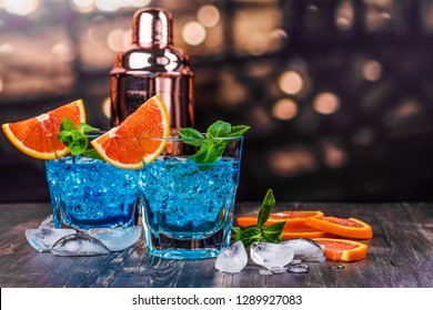 Blue lagoon cocktail in a glass on blured bar background. Blue hawaii cocktail with ice cubes and orange slices