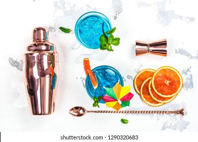Blue lagoon cocktail in a glass on white background. Blue hawaii cocktail with ice cubes and orange slices