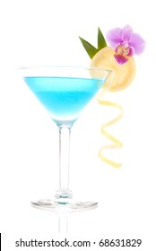 Blue lagoon cocktail with vodka, triple sec, white cranberry juice, lime, lemon wheel, pineapple leaf and orchid in martini glass isolated on a white background
