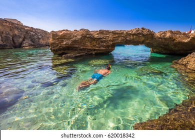 Blue Lagoon, Malta - Snorkeling tourist at the caves of the Blue Lagoon on the island of Comino on a bright sunny summer day with blue sky