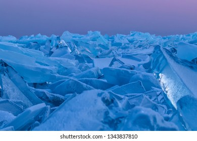 Blue Lake Baikal hummocks at sunset on a background of pink heaven