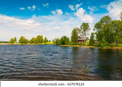 Blue lake Kizhi in Karelia. North country Russia.  Amazing beautiful rural landscape.  Green grass and trees in meadow. Pure water. Sunny day.