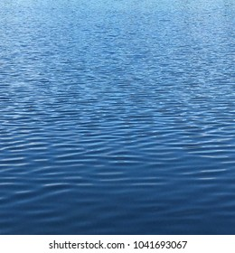 Blue lake or ocean water background with ripples with space for text
