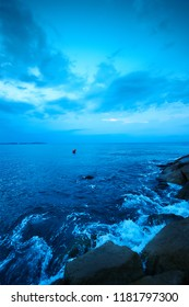 Blue lanscape with crashing waves and horizon before sunrise and res arrow shaped buoy in the center
