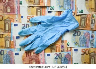 Gant chirurgical en latex bleu posé sur la monnaie de l'Union européenne Euro différents billets de papier