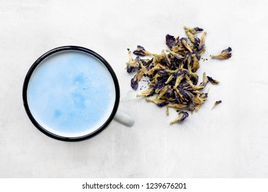 Blue latte on concrete table. Butterfly pea (clitoria) herbal milky beverage.