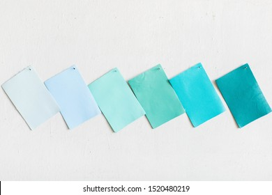 Blue leather cowhide swatches on white wall, copy space