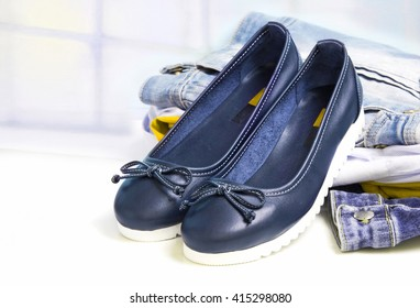 Blue leather flat sport style ballerinas on a stack of jeans cloth light background empty copy space for text.