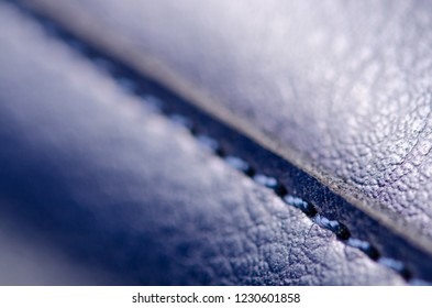 Blue leather material textile fabric bag accessory firmware stitches macro on blur background