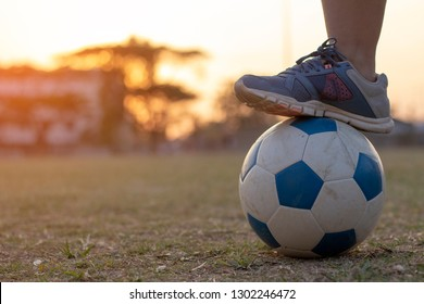 Blue leather soccer ball on the lawn at sunset