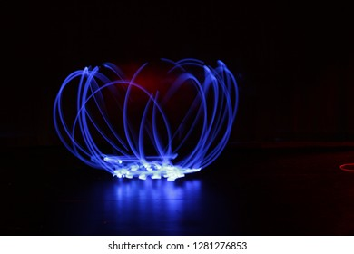 Blue led light trails create an abstract flower on a black background.