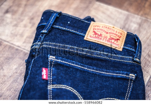 Blue Levis jeans with pocket on dark wooden background. Selectible focus.