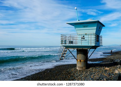Blue lifeguard tower number 4 on a rocky sand beach with clouded blue sky sunny end of day, on Torrey Pines State Beach in California, located in San Diego County.