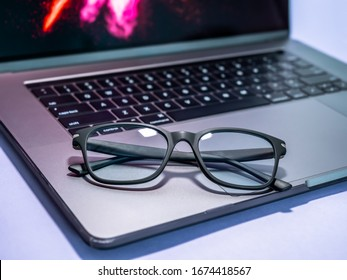 Blue light blocking glasses on the laptop. Black frame glasses for filtering blue light from the computer. Prevent Computer Vision Syndrome. Eye protection from PC screen