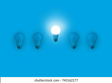 Blue light bulbs with glowing one different idea on blue background. minimal concept. top view. New Creative Idea